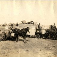 Dump at 133rd Street & Harlem River, Bronx. Men wait on horse-drawn wagons loaded with garbage. May 1925.
