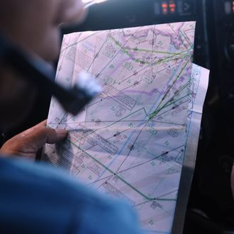 A pilot uses a map on board a Vietnamese Air Force Russian-made AN-27 aircraft during a search flight over Vietnam's southern sea aimed at finding the Malaysia Airlines' missing flight MH370 on March 14, 2014. The needle-in-a-haystack hunt for the missing Malaysian airliner spread to the vast Indian Ocean after the White House cited