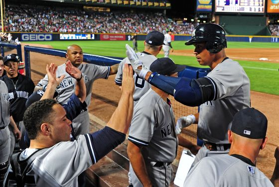 Alex Rodriguez #13 of the New York Yankees is congratulated by teammates after hitting an 8th inning grand slam against the Atlanta Braves at Turner Field on June 12, 2012 in Atlanta, Georgia.