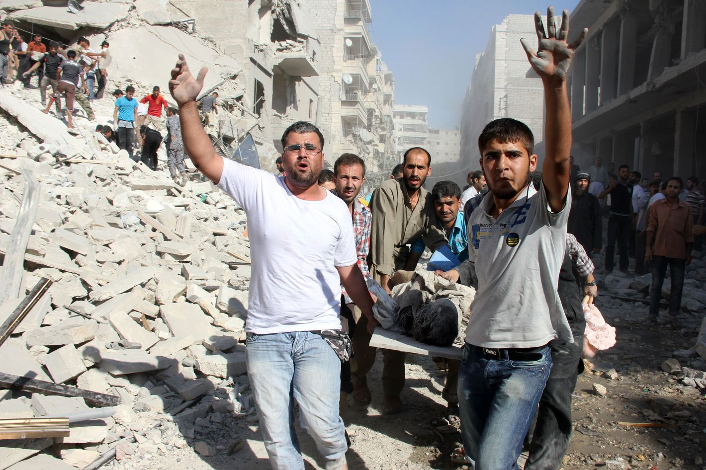 Syrian men evacuate a victim following an air strike by regime forces in the northern city of Aleppo on August 26, 2013. Syria's opposition accused pro-regime forces of opening fire at UN weapons inspectors on their way to a suspected chemical weapons site outside Damascus in a bid to hinder their investigation. AFP PHOTO/ABO AL-NUR SADK        (Photo credit should read ABO AL-NUR SADK/AFP/Getty Images)