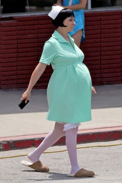 Joaquin Phoenix gets into character while carrying his boots and walking barefoot on the set of 'Inherent Vice' in Los Angeles. Maya Rudolph, who is expecting her fourth child with the film's director Paul Thomas Anderson, showed off a huge baby bump in green scrubs as she walked around set.