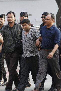 Property tycoon Sohel Rana (C) is escorted to a press conference at the Rapic Action Battalion (RAB) headquarters in Dhaka on April 28, 2013.    Bangladesh police on Sunday arrested the owner of a garment factory block that collapsed last week killing more than 375 people as hopes faded for survivors at the disaster site.        (Photo credit should read STR/AFP/Getty Images)