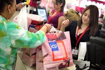 Lisette Barraza (R) hands a shopper her merchadise in a bag displaying the new store logo at a JCPenney store in the North Riverside Park Mall February 1, 2012 in North Riverside, Illinois. J.C. Penney Company Inc., the parent company of JCPenney, today rolled out a major transformation of its JCPenney stores which included a new pricing structure that offers fewer sales, monthly specials, and more predictable pricing. The stores will also add new merchandise brands to their existing lines and display the new store logo.
