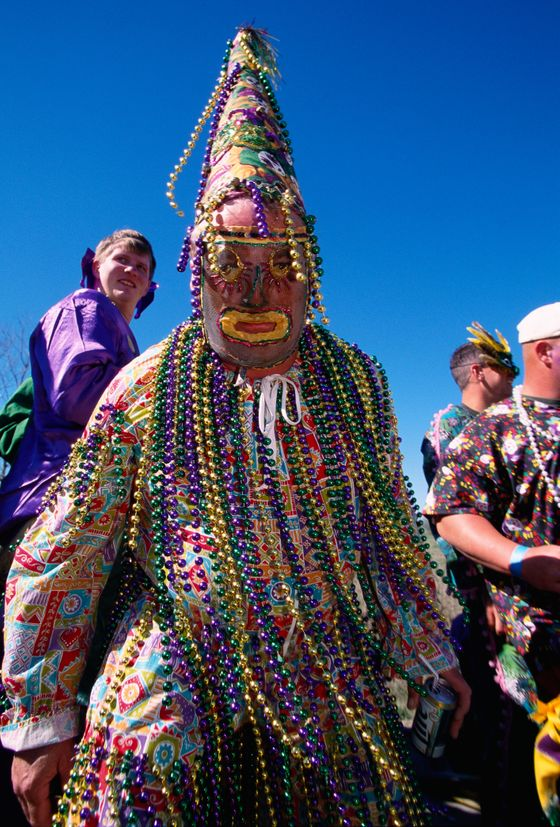 ca. 1999, Church Point, Louisiana, USA --- A heavily beaded Mardi Gras reveler attends Courir de Mardi Gras at Church Point. The Louisiana men wear costumes and roam the area, stopping at homes to perform dances and antics in return for the gift of an ingredient for gumbo. --- Image by © Philip Gould/Corbis