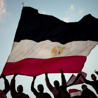 Anti-government demonstrators wave an Egyptian flag in Tahrir Square on February 11, 2011 in Cairo, Egypt. After 18 days of widespread protests, Egyptian President Hosni Mubarak, who has now left Cairo for his home in the Egyptian resort town of Sharm el-Sheik, announced that he would step down.