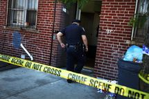 Police stand near the scene of a murder in the Brooklyn borough of New York City.