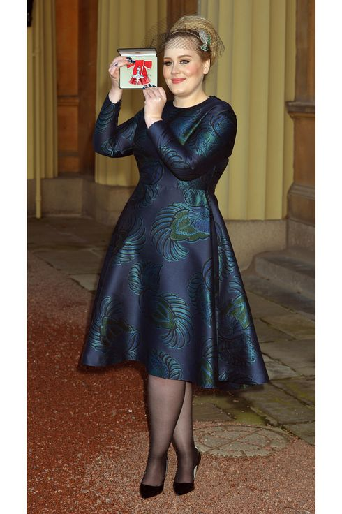 British singer-songwriter Adele Adkins holds her medal after being appointed a Member of the Order of the British Empire (MBE) for services to music presented to her by the Prince Charles, Prince of Wales during an investiture ceremony at Buckingham Palace in London on December 19, 2013.