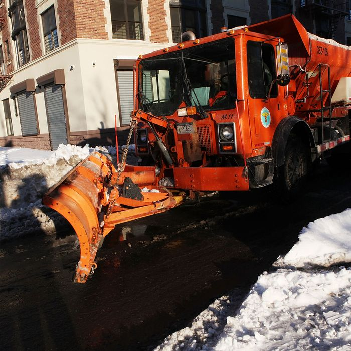 A plow clears the road of snow at the intersection of 126th Street and 5th Avenue on December 28, 2010 in New York City.