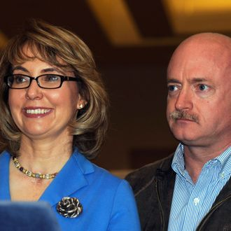 U.S. Rep. Gabrielle Giffords, left, and her husband Mark Kelly appear at a news conference following a tour of the New EastCoast Arms Collectors Associates arms fair in Saratoga Springs, N.Y. on Sunday, Oct. 13, 2013.