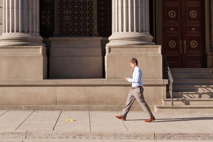 Man texting and walking near a banana peel