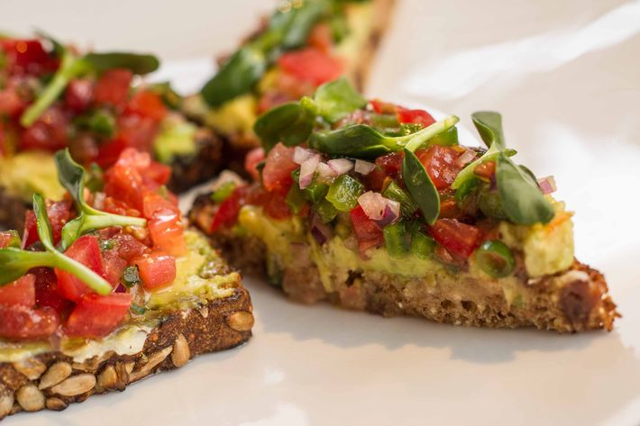 Avocado toast with cumin butter on multigrain bread, sunflower shoots, and pico de gallo.