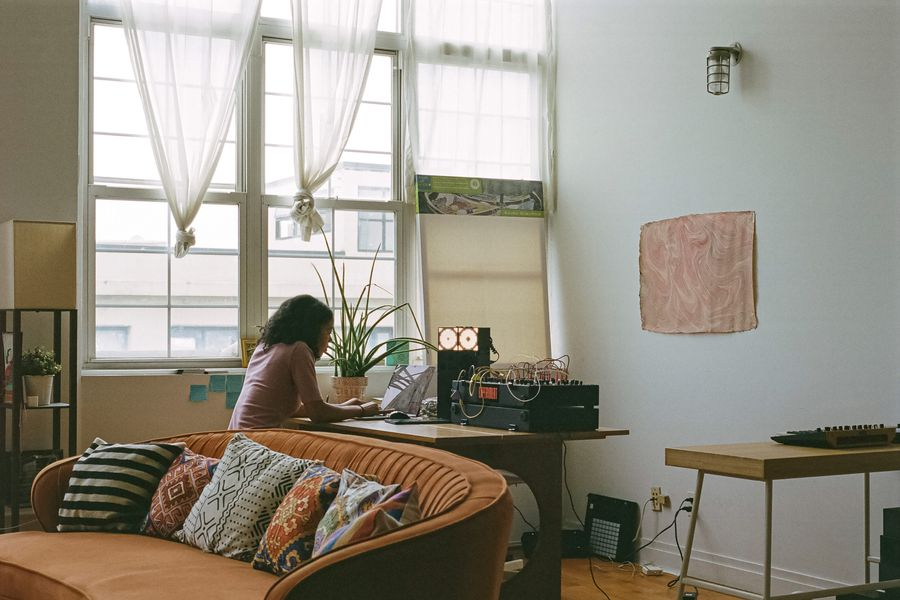 A woman sitting at a table with a laptop and modular synthesizer on top of it. A curvy, orange sofa with African patterned throw pillows is in the foreground