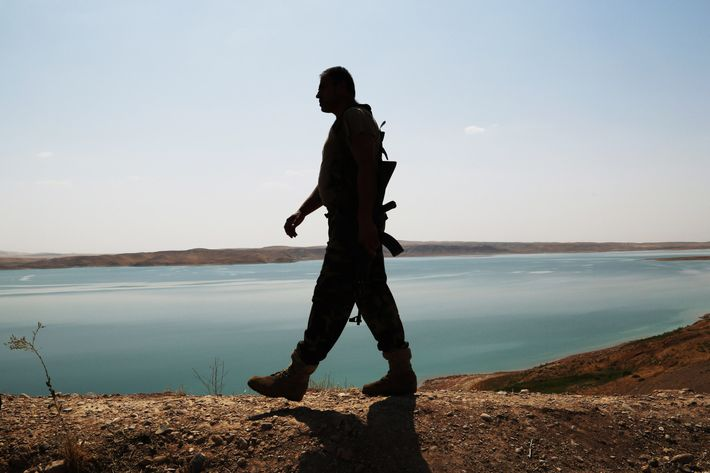 A Kurdish peshmerga fighter patrols near the Mosul Dam at the town of Chamibarakat outside Mosul, Iraq, Sunday, Aug. 17, 2014.