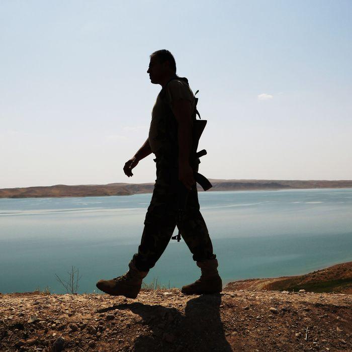 A Kurdish peshmerga fighter patrols near the Mosul Dam at the town of Chamibarakat outside Mosul, Iraq, Sunday, Aug. 17, 2014.