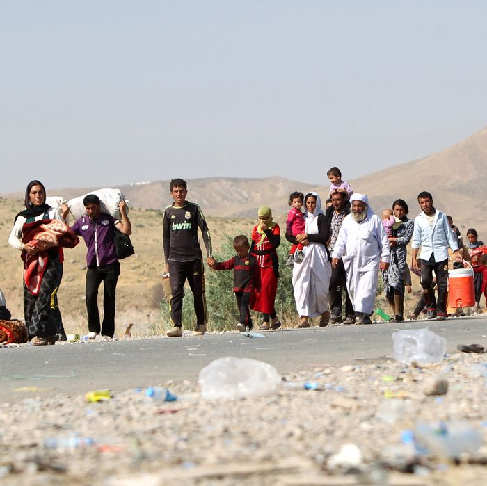 Displaced Iraqi families from the Yazidi community cross the Iraqi-Syrian border at the Fishkhabur crossing, in northern Iraq, on August 13, 2014. At least 20,000 civilians, most of whom are from the Yazidi community, who had been besieged by jihadists on a mountain in northern Iraq have safely escaped to Syria and been escorted by Kurdish forces back into Iraq, officials said. The breakthrough coincided with US air raids on Islamic State fighters in the Sinjar area of northwestern Iraq on August 9, and Kurdish forces from Iraq, Syria and Turkey working together to break the siege of Mount Sinjar and rescue the displaced AFP PHOTO/AHMAD AL-RUBAYE (Photo credit should read AHMAD AL-RUBAYE/AFP/Getty Images)