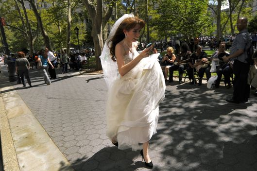 A bride in her wedding dress runs from the courthouse in Lower Manhattan in  New York August 23, 2011.  One of the strongest earthquakes to strike the US east coast in decades rattled offices Tuesday in downtown Washington and caused panicked evacuations from skyscrapers as far away as New York. The Pentagon, the US Capitol and Union Station in the nation's capital were all evacuated after the 5.9-magnitude quake, which was shallow with its epicenter only 0.6 miles (one kilometer) underground. The disruption to cell phone services in the hour after the quake added to the sense of panic in a country preparing to mark the 10th anniversary of the September 11, 2001 terror attacks. AFP PHOTO/TIMOTHY A.CLARY (Photo credit should read TIMOTHY A. CLARY/AFP/Getty Images)