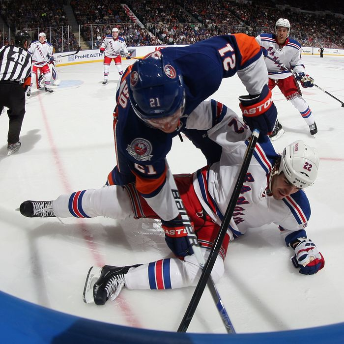 UNIONDALE, NY - OCTOBER 15: Kyle Okposo #21 of the New York Islanders hits Brian Boyle #22 of the New York Rangers at the Nassau Veterans Memorial Coliseum on October 15, 2011 in Uniondale, New York. (Photo by Bruce Bennett/Getty Images)