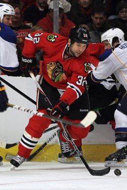 John Scott #32 of the Chicago Blackhawks controls the puck in the St. Louis Blues zone at the United Center on February 19, 2012 in Chicago, Illinois. The Blackhawks defeated the Blues 3-1.