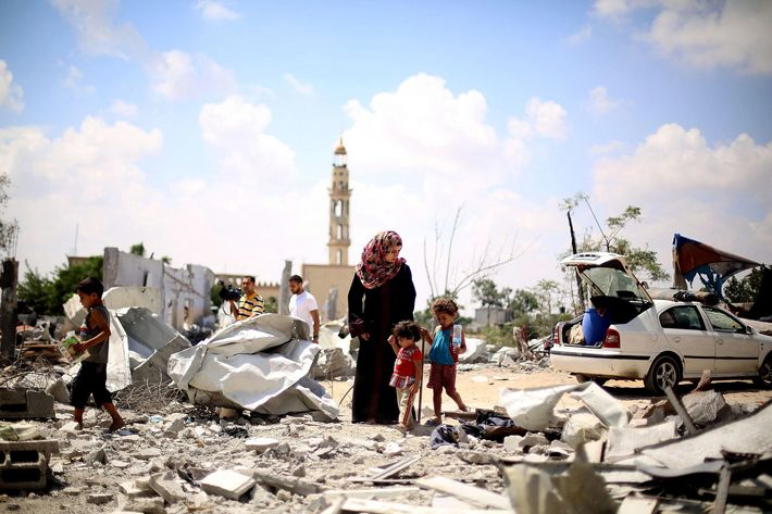 Palestinians walk through the ruins of their buildings during a cease-fire which starts at 10 o'clock in the morning in Beit Lahia, Gaza on August 04, 2014. Palestinians try to collect usable belongings amongst the ruins and held funeral ceremonies of their relatives killed by Israeli strikes, during the truce.