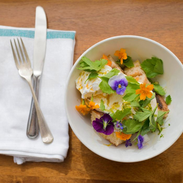 The signature dish of poached eggs over avocado with yogurt, lardons, croutons, lime vest, fresh herbs, and housemade chili oil.