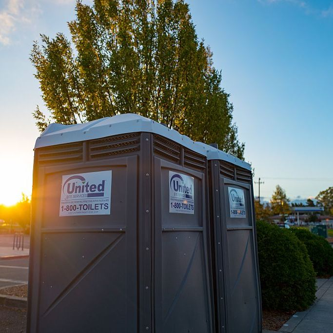 Portable Toilets Standing Tall At Sunset