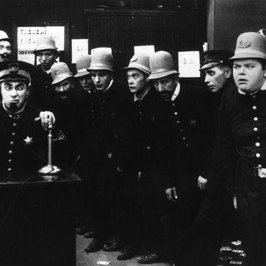 A scene from 'In the Clutches of the Gang', a Keystone Cops silent comedy directed by George Nichols and Mack Sennett. Left to right : Ford Sterling (on phone), Edgar Kennedy, George Jeskey, Al St John, Hank Mann, Rube Miller, and Roscoe Fatty Arbuckle (1887 - 1933).   (Photo by Hulton Archive/Getty Images)