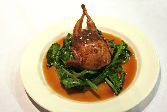 Masak's roasted quail stuffed with rice, chestnut, lotus seed, salted duck yolk, and kale.
