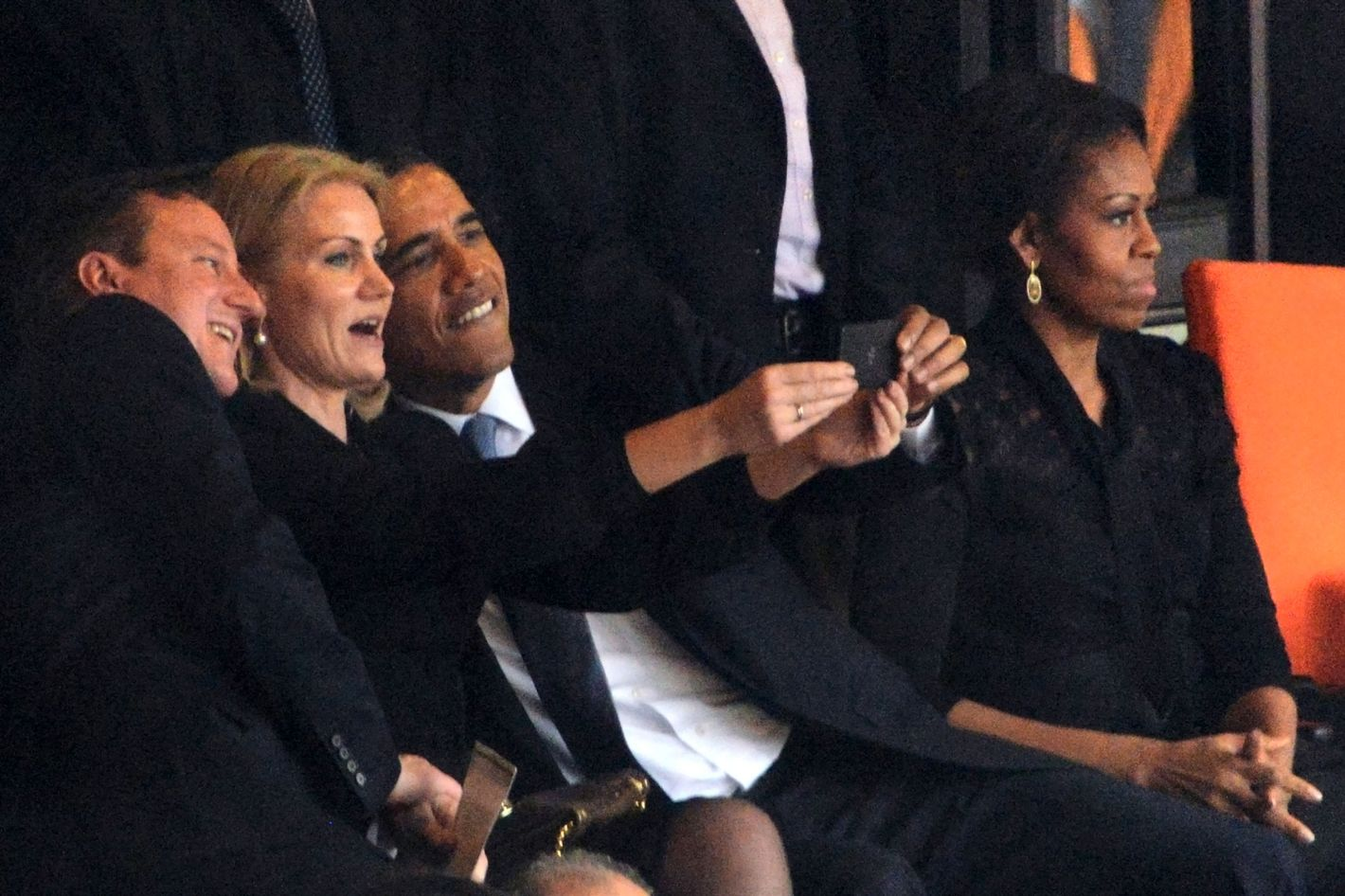 US President  Barack Obama (R) and British Prime Minister David Cameron pose for a picture with Denmark's Prime Minister Helle Thorning Schmidt (C) next to US First Lady Michelle Obama (R) during the memorial service of South African former president Nelson Mandela at the FNB Stadium (Soccer City) in Johannesburg on December 10, 2013. Mandela, the revered icon of the anti-apartheid struggle in South Africa and one of the towering political figures of the 20th century, died in Johannesburg on December 5 at age 95.
