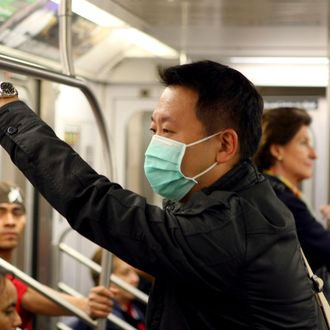 Kenny Tsang wears a protective face mask while riding the subway in New York, USA, 29 April 2009.