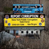 In this Wednesday, Jan. 27, 2016, photo, a billboard with a message about reporting public corruption, left, stands along Interstate 90 in Albany, N.Y. Authorities in New York's corruption-plagued capital city are using billboards to urge citizens to report crooked politicians, using a tactic more commonly employed to find missing people or fight drunk driving. (AP Photo/Mike Groll)