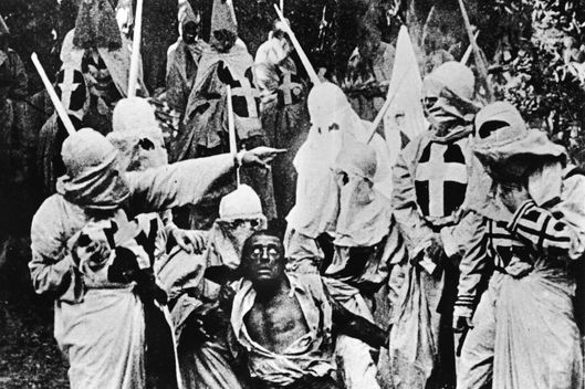 Actors costumed in the full regalia of the Ku Klux Klan chase down a white actor in blackface in a still from 'The Birth of a Nation,' the first-ever feature-length film, directed by D. W. Griffith, California, 1914.