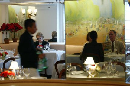 NEW YORK, UNITED STATES:  A waiter tends to customers at La Caravelle, a temple of French cuisine, during lunch time in Manhattan 21 May, 2004. La Caravelle, opened in 1960 and owned by Rita and Andre Jammet since 1988, will close its doors later 21 May after a last dinner and over 44 years in business. The economic crisis in the city, retiring chefs and new tastes among restaurant goers are reportedly the reasons that have pushed several French restaurants such as La Caravelle, the Lutece, La Cote Basque, and Lespinasse, to go out of business. AFP PHOTO Timothy A. CLARY  (Photo credit should read TIMOTHY A. CLARY/AFP/Getty Images)