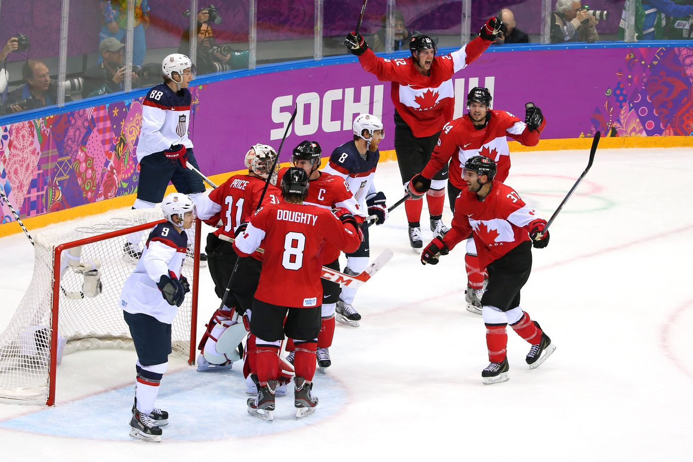 Patrick Kane #88 and Zach Parise #9 of the United States react as Carey Price #31, Drew Doughty #8 and Sidney Crosby #87 of Canada celebrate after defeating the United States 1-0 during the Men's Ice Hockey Semifinal Playoff on Day 14 of the 2014 Sochi Winter Olympics at Bolshoy Ice Dome on February 21, 2014 in Sochi, Russia.