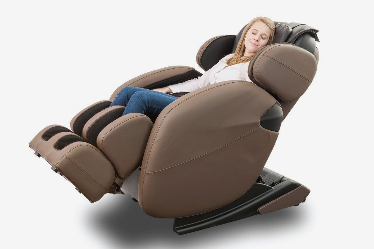 A smiling woman sits in the brown massage chair with her eyes closed.