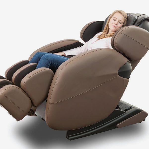 Une femme souriante est assise dans le fauteuil de massage brun, les yeux fermés.