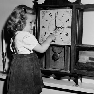 Girl (4-5) adjusting clock
