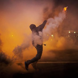 A protester throws a gas canister back at police during clashes at North Ave and Pennsylvania Ave in Baltimore