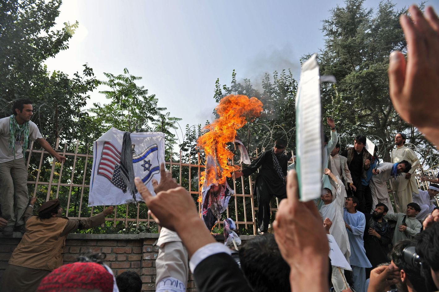 "Afghan demonstrators torch a portrait of US President Barack Obama as another demonstrator (bottom L) prepares to burn a depiction of US and Israeli flags in Kabul on September 16, 2012. Hundreds of students poured into the streets of Kabul September 16 shouting anti-US slogans to protest against a film mocking Islam that has sparked deadly riots in the Middle East and North Africa, police said. The protesters, mostly students from Kabul University, shouted ""death to America"" as they blocked a road near their compound."