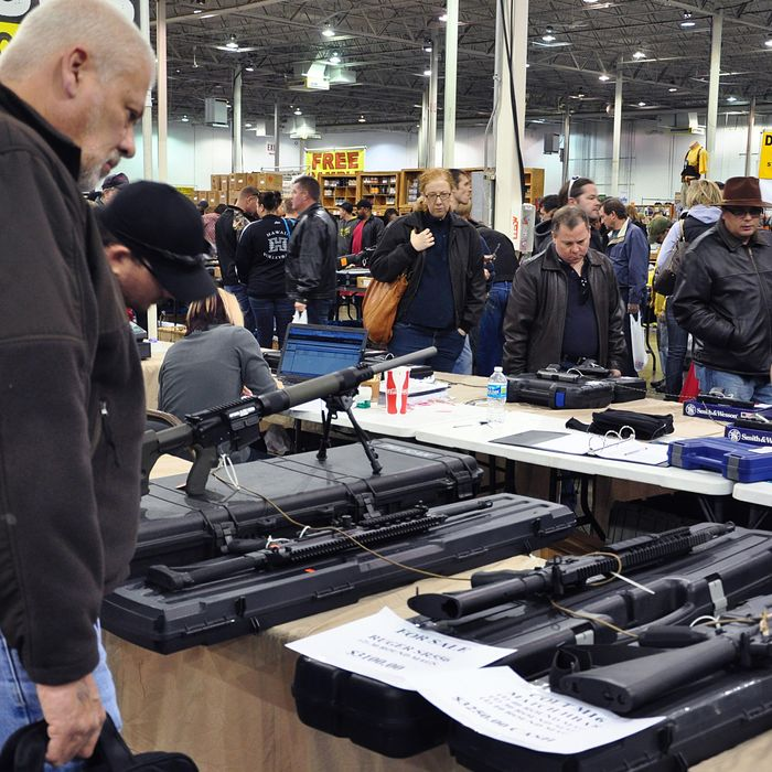 Gun show goers look at various assault-style weapons December 30, 2012 at the Nation's Gun Show in Chantilly, Virginia. Since the Connecticut school shootings, gun sales, particularly assault-style weapons have gone up sharply.
