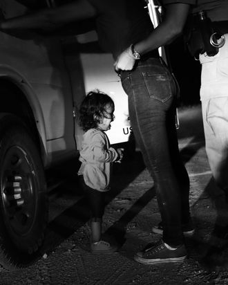 A 2-year-old girl crying as a Border Patrol agent pats down her mother.