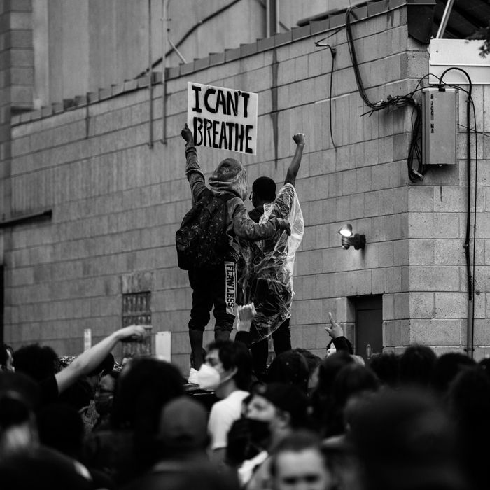 """ID: Embodying the God who is Justice: Agitator, Educator, Organizer,  a black and white picture of a protest against the murder of George Floyd shows a crowd of people with two, both with dark skin and layers of clothing on, standing above the rest. The one on the left holds up a white sign with dark letters that reads """"I CAN'T BREATHE"""" and has an arm around the one on the right, who is wearing a rain poncho and has an arm raised, fist in the air."""
