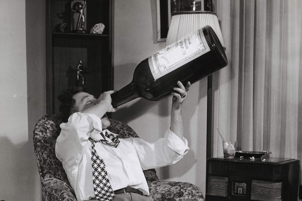 Young man drinking alcohol from a huge bottle