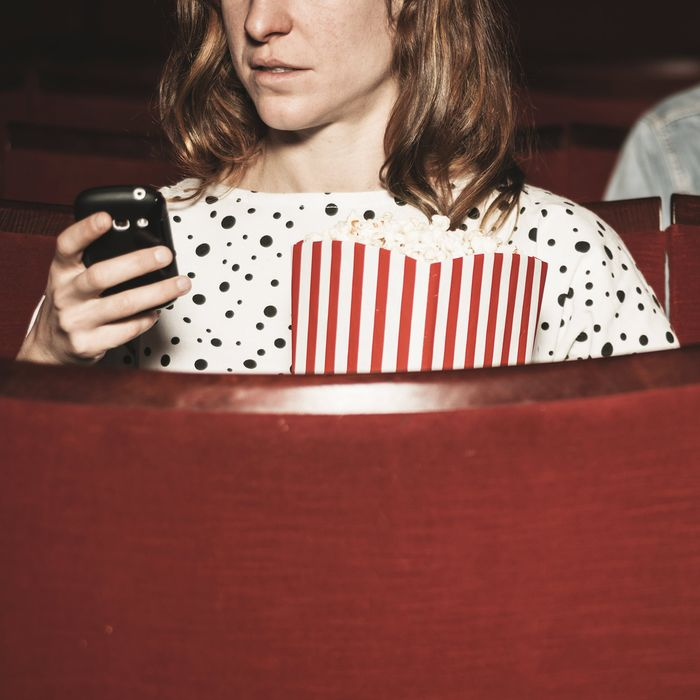 Man and woman using their phones in theater
