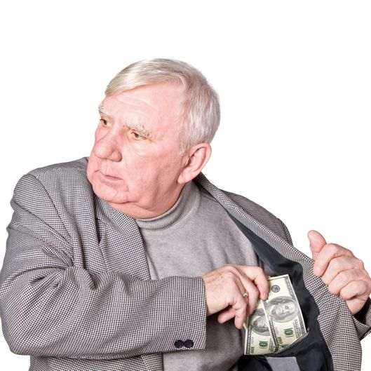 Elderly man puts money in an internal pocket of a jacket. It is isolated on a white background