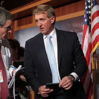 U.S. Sen. Jeff Flake (R-AZ) (R) talks to a reporter at the end of a news conference March 6, 2013 on Capitol Hill in Washington, DC. The senators held a news conference on legislation to prevent gun violence.