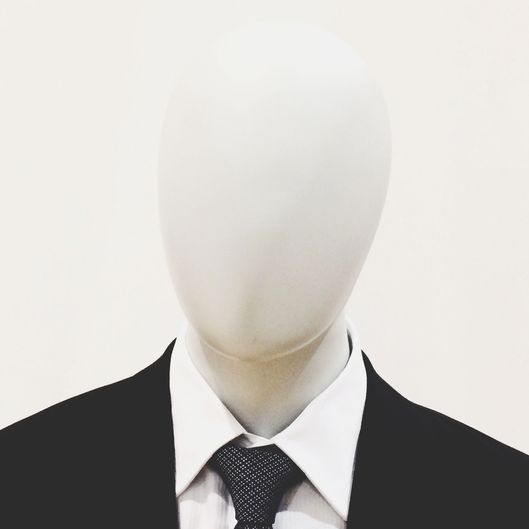 Close-Up Of Mannequin Dressed In Suit Against White Background