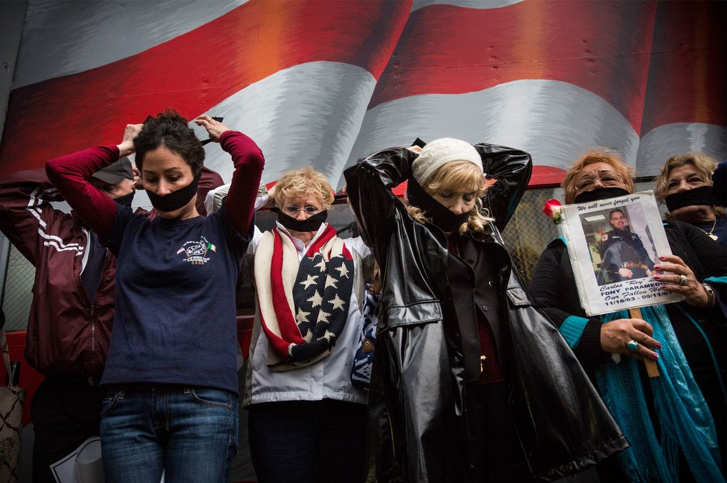 NEW YORK, NY - MAY 10:  Family members of victims of the September 11, 2001 attacks tie gags around their mouths to protest the decision by city officials to keep unidentified human remains of the 9-11 victims at the 9-11 Museum at the World Trade Center site, on May 10, 2014 in New York City. The decision by city officials to keep the remains at the museum until they are able to be identified has drawn both support and criticism by families of victims. The remains were moved early this morning from the medical examiner's repository to the 9-11 Museum.  (Photo by Andrew Burton/Getty Images)