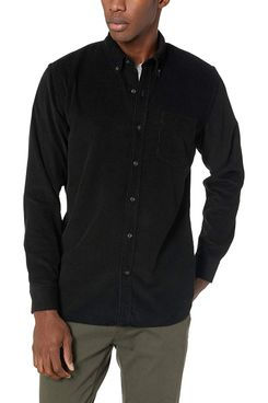 A male model wearing a men's standard-fit long sleeve black corduroy shirt with a collar over a light grey t-shirt from Goodthreads and a pair of grey trousers. The Strategist - A Bunch of Men's Button Downs (From $16) Are on Sale at Amazon.