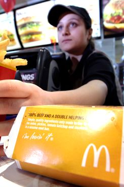 A McDonald's employee serves a burger and a carton of french fries at one of the company's restaurants in London, U.K., on Monday, Feb. 1, 2010.