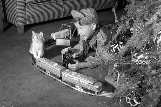 1950s boy in engineer outfit playing with electric train set by christmas tree and kitten indoor